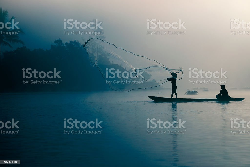 Fisherman casting out fishing net stock photo