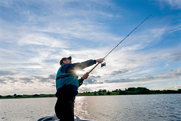 fisherman casting seine linie - angeln dänemark stock-fotos und bilder