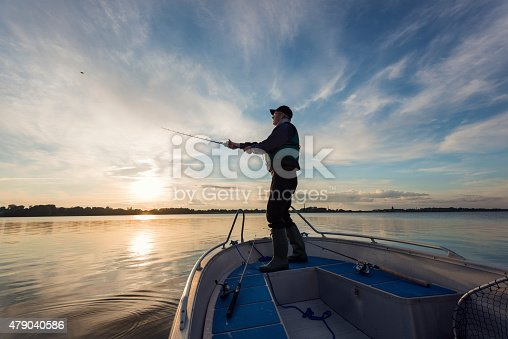 Portrait of a 65 year old  fisherman casting out his  fishing line into the water from his boat into a flat calm sea. Horizontal format photographed against a setting sun with lots of copy space in the sky. Photographed on Stege Nor on the island of Møn or Moen in Denmark.