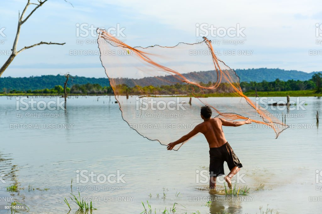 Fisherman  casting traditional fishing net to fish stock photo