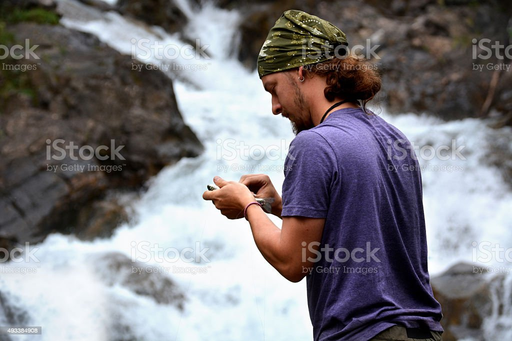 Fisherman Catches Fish in Waterfall: Closeup stock photo