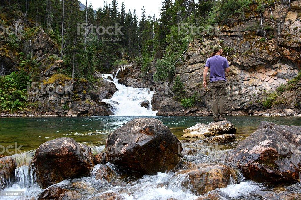 Fisherman Catches Fish in Waterfall stock photo