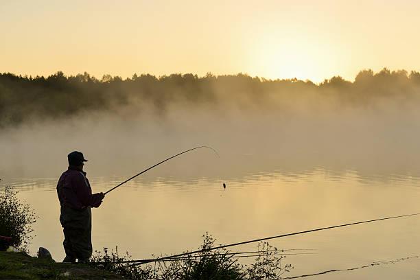 pescador de capturas de peixes no lago ao pôr do sol - fishman imagens e fotografias de stock