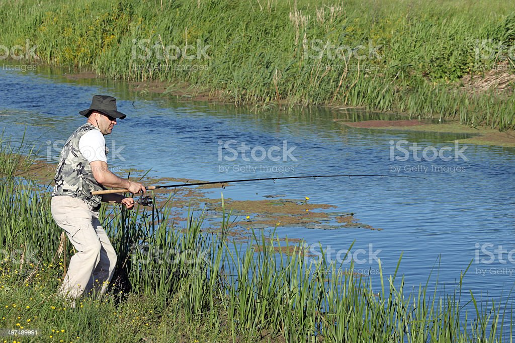 fisherman catching fish on river royalty-free stock photo
