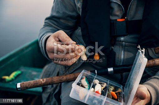 115874504istockphoto Fisherman changing soft lure on spinning 1177161195
