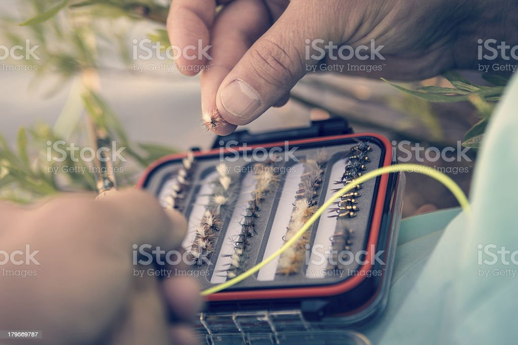 Fisherman choosing lure from tackle box while fly fishing royalty-free stock photo