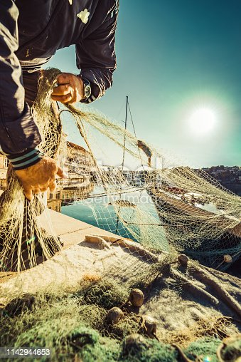 Fisherman in the morning cleaning the fishnet from the fish.