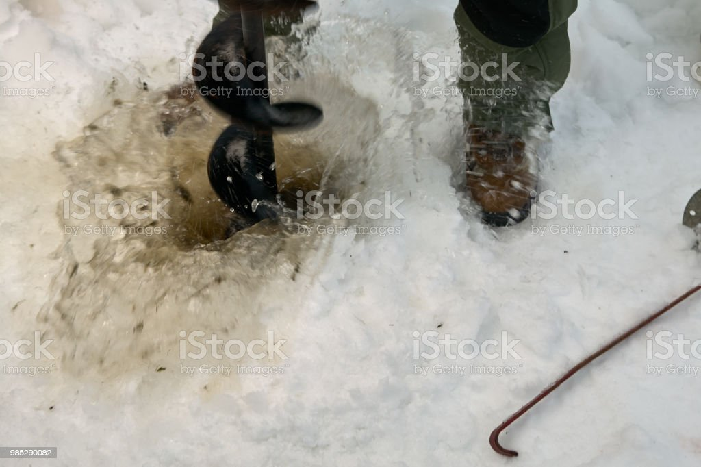 Fisherman cutting a hole through ice with an augur stock photo