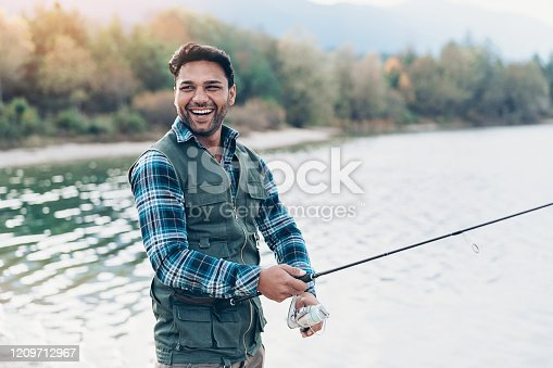 Smiling young man with fishing rod by the river