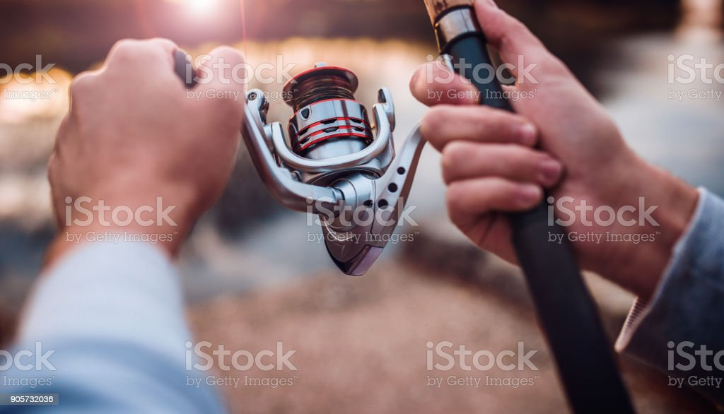 Fisherman enjoys in fishing on the river, close up photo. Sport, recreation, lifestyle stock photo