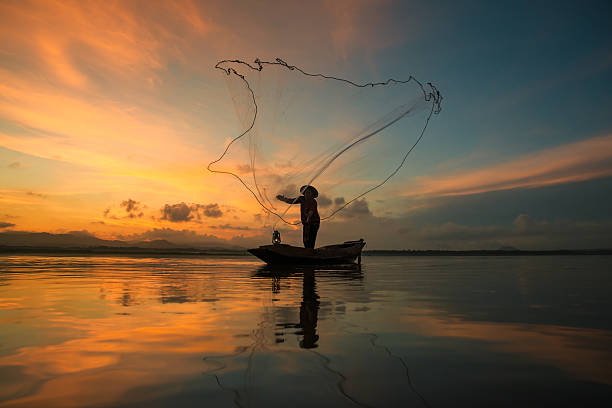 Fisherman fishing at lake in Morning, Thailand. Fisherman fishing at lake in Morning, Thailand. fisherman stock pictures, royalty-free photos & images
