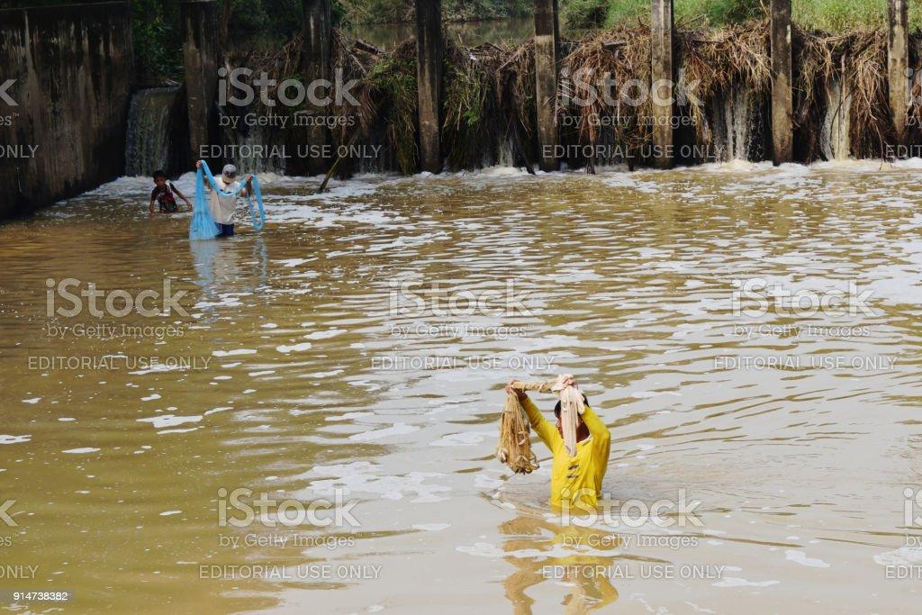 Fisherman fishing by the net in turbid water stock photo