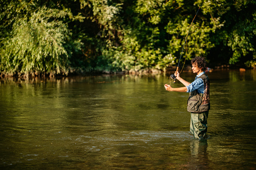 Fisherman in action. Guy is throwing spoon of fly rod in water and holding part of it in hand. Man wears special protection clothes