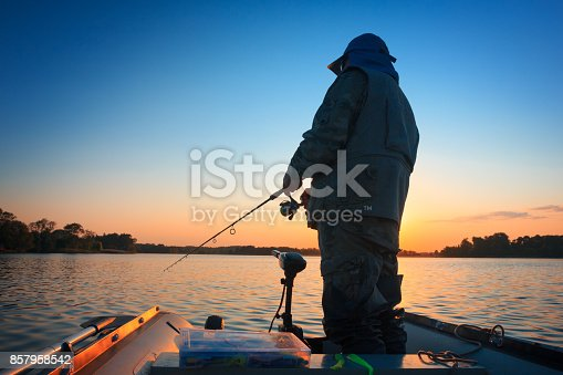 951984746 istock photo A fisherman fishing in a lake at sunset 857958542