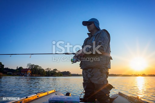 951984746 istock photo A fisherman fishing in a lake at sunset 857958628