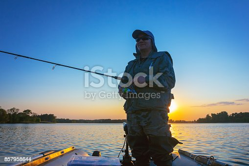 688562434 istock photo A fisherman fishing in a lake at sunset 857958644