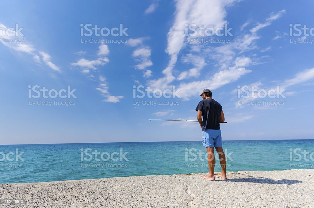 Fisherman fishing on a seaside bank. royalty-free stock photo