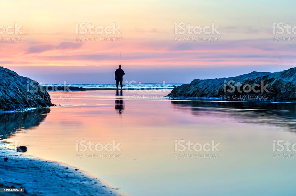 Fisherman fishing on the waterfront and admiring the sunset. zbiór zdjęć royalty-free