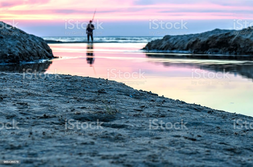 Pêcheur de pêche sur le front de mer et admirer le coucher du soleil. - Photo de Admiration libre de droits