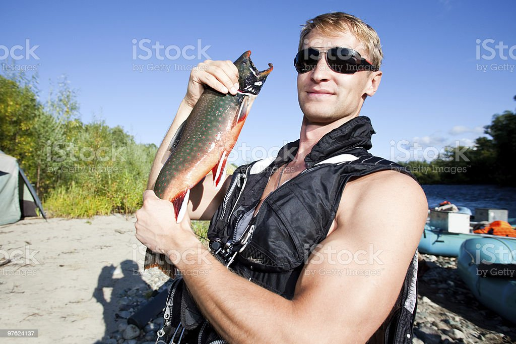 fisherman holding a fresh caught fish royalty-free stock photo