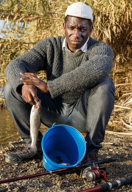 fisherman holding fish in his hands - fishman imagens e fotografias de stock