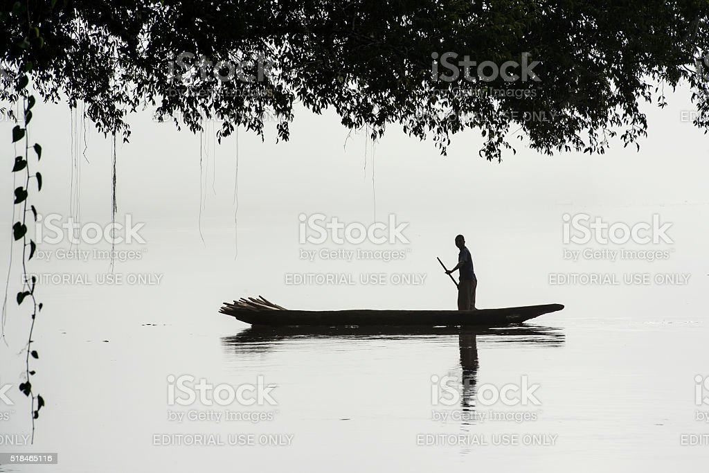 Fisherman in a pirogue on the foggy Congo River stock photo