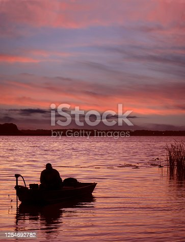 175421347 istock photo Fisherman in a Small Boat Starts His Day with a Beautiful Sunrise on the Lake 1254692782