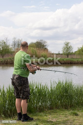 139888169 istock photo Fisherman in action, Fisherman holding rod in action 520978410