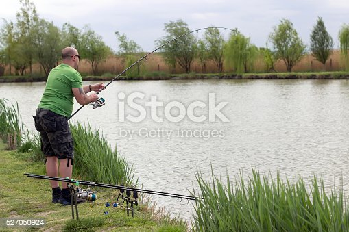 139888169 istock photo Fisherman in action, Fisherman holding rod in action 527050924