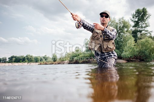 Fisherman in action. Guy is throwing spoon of fly rod in water and holding part of it in hand. He looks straight forward. Man wears special protection clothes