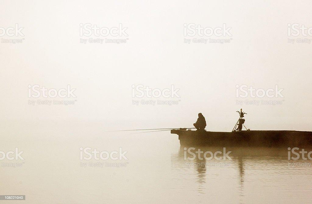 Fisherman in boat on foggy morning stock photo