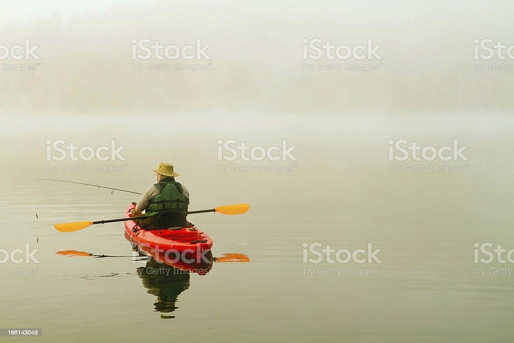 fisherman in red kayak, morning fog, reflection royalty-free stock photo