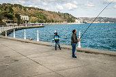 Istanbul, Turkey - March 27, 2016: Man is fishing on the coast of Bosphorus in Tarabya, Istanbul, Turkey