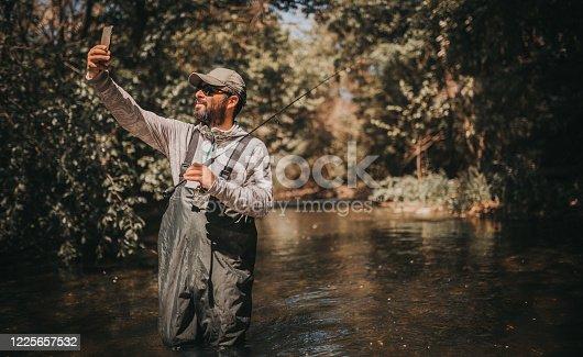 992209122 istock photo Fisherman making a selfie 1225657532