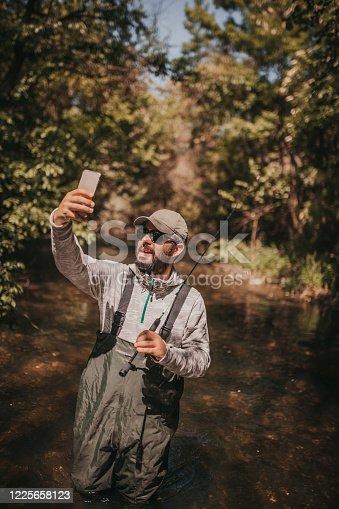 992209122 istock photo Fisherman making a selfie 1225658123
