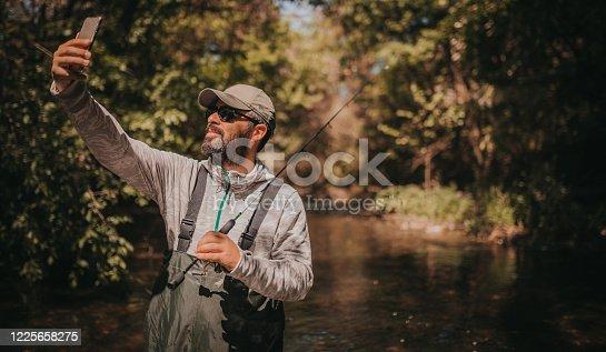 992209122 istock photo Fisherman making a selfie 1225658275