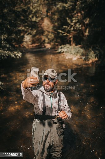 992209122 istock photo Fisherman making a selfie 1225659215