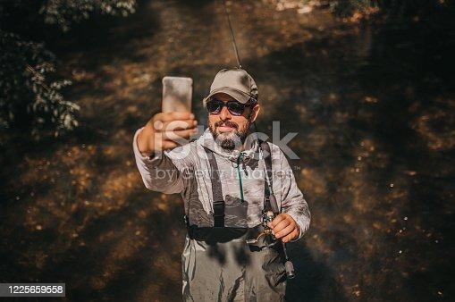 992209122 istock photo Fisherman making a selfie 1225659558