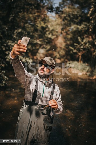 992209122 istock photo Fisherman making a selfie 1225659567