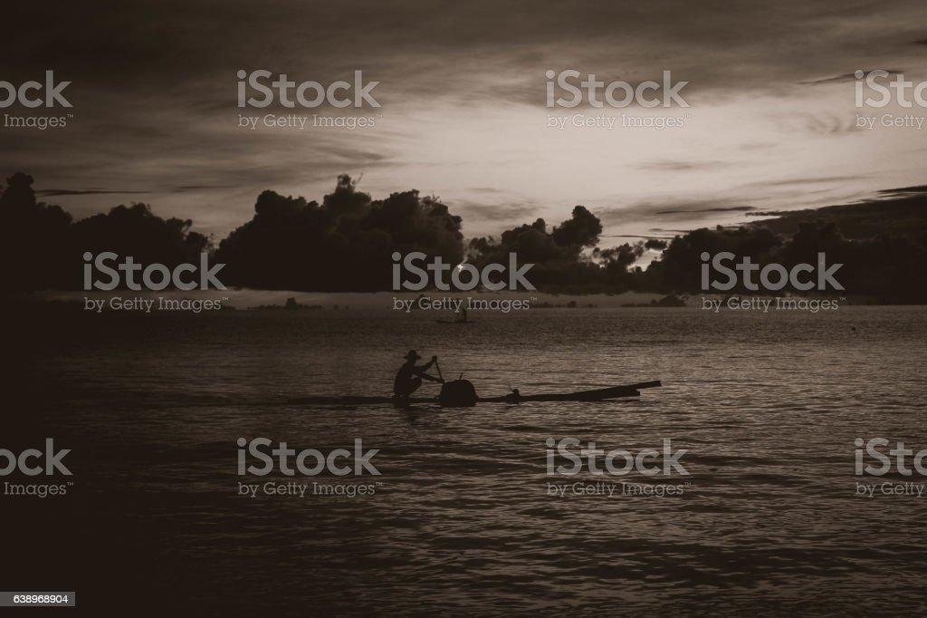 Fisherman Maneuvering a boat during a sunrise Seascape. stock photo