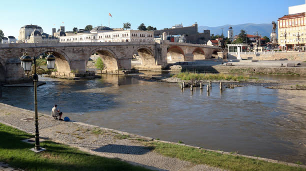 yaz günü mavi gökyüzü ile makedonya arkeoloji müzesi yakınlarındaki üsküp şehir merkezinde vardar nehri üzerinde taş köprü yakınında balıkçı - üsküp stok fotoğraflar ve resimler