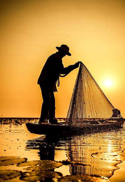 Fisherman of Lake in action when fishing stock photo