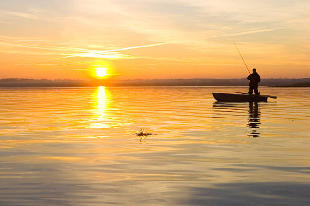 Fisherman on a boat at sunset fisherman on boat. catching pike freshwater fishing stock pictures, royalty-free photos & images