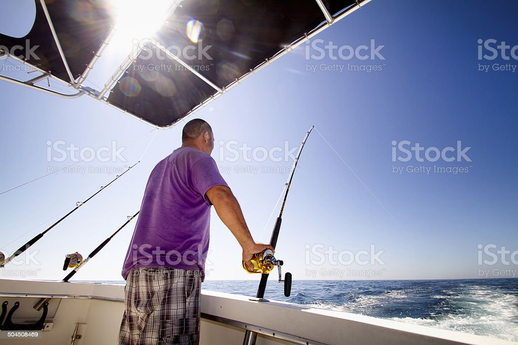 Fisherman on a boat in the ocean stock photo