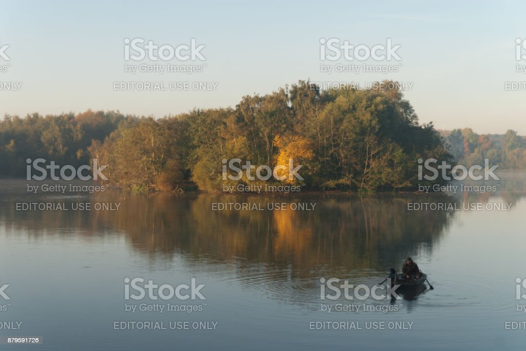 Fisherman on a lake on an autumny day stock photo