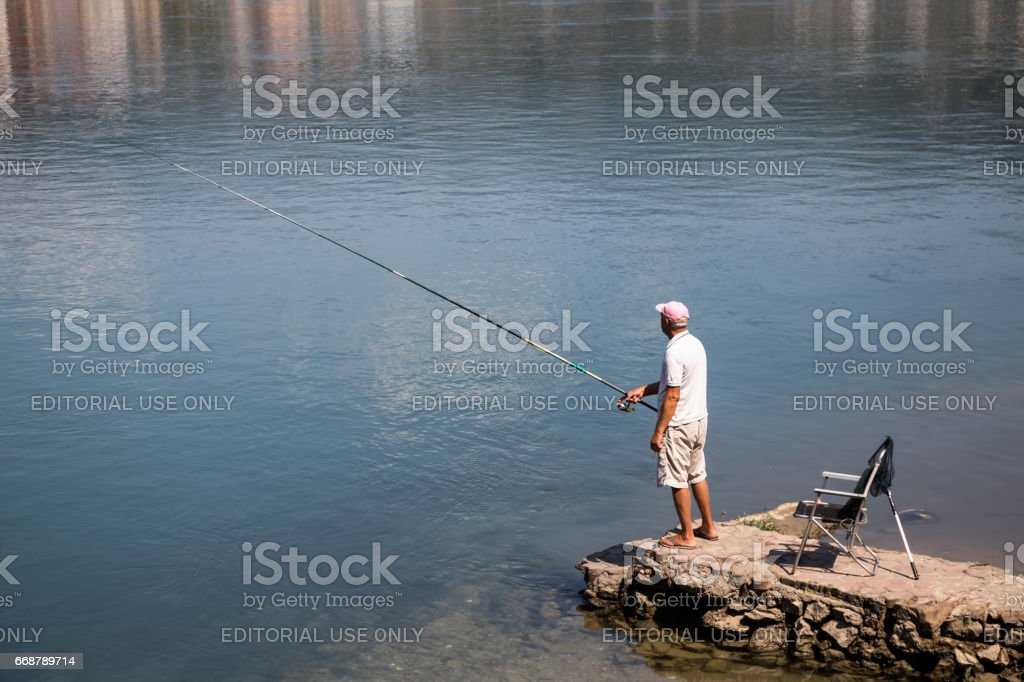 Fisherman on a pier stock photo