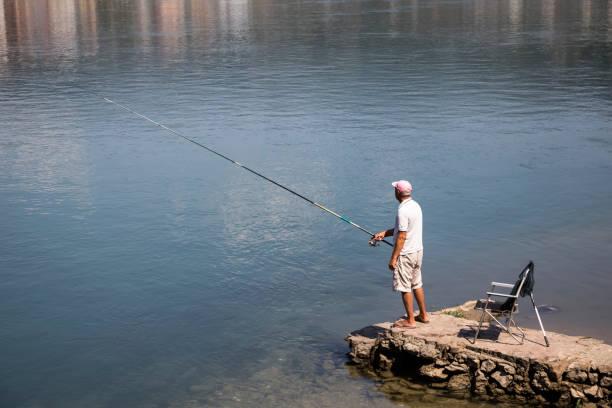 Fisherman on a pier stock photo