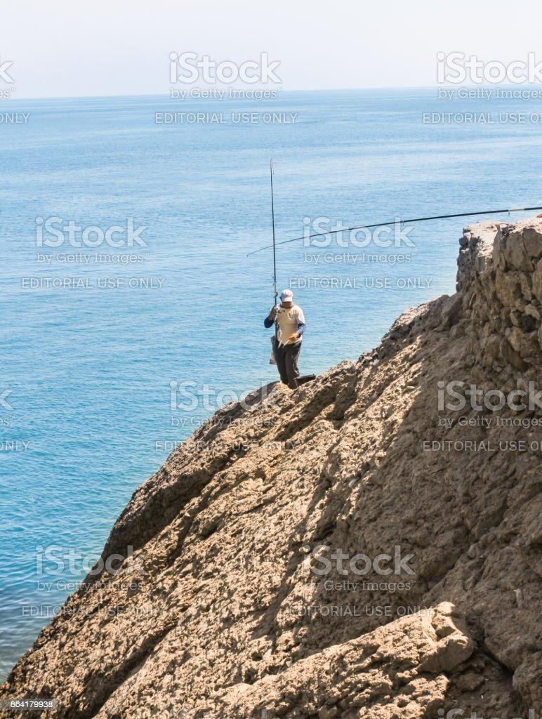 Fisherman on a rock. royalty-free stock photo