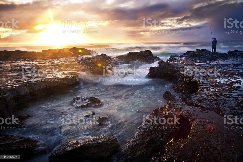 A fisherman on a rocky outcrop on the seashore at sunrise royalty-free stock photo