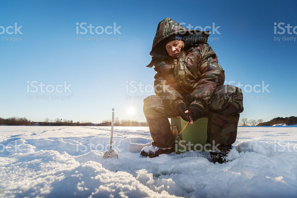 Fisherman on a winter lake stock photo